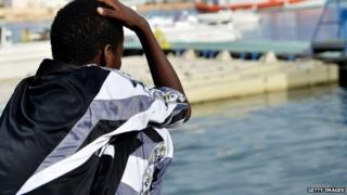 A young survivor of a shipwreck of migrants off immigrants off the Italian coast looks out over the water of Lampedusa on 8 October 2013