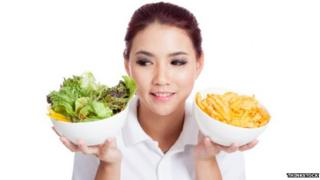 Woman choosing between salad or chips