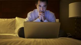 A man in a hotel room looks at a laptop.