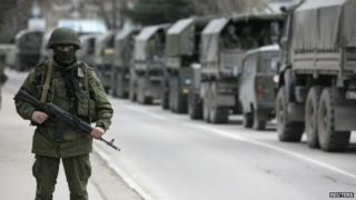 File photo: Armed Russian soldier stands near Russian army vehicles outside a Ukrainian border guard post in the Crimean town of Balaclava, 1 March 2014