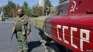 An armed pro-Russian separatist stands next to an APC in the city of Donetsk