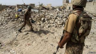 Pakistani soldiers stand near the debris of a house which was destroyed during a military operation against Taliban militants in the town of Miranshah in North Waziristan July 9, 2014.