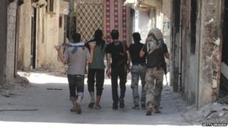 Rebel fighters walk holding their weapons to a position on a front-line in a rebel-held suburb of Damascus