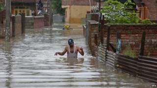A Kashmiri man wades through flood water in the outskirts of Srinagar, the summer capital of Indian Kashmir on 04 September 2014.