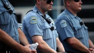 Police officers wear what appear to be body cameras as they hold the line against protesters gathered at the police station during a rally in Ferguson, Missouri 30 August 2014