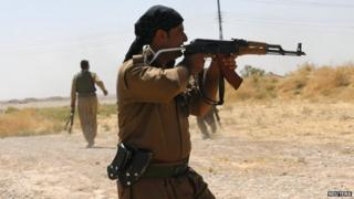 A Kurdish fighter shoots towards Islamic State gunmen during clashes in northern Iraq - 4 September 2014