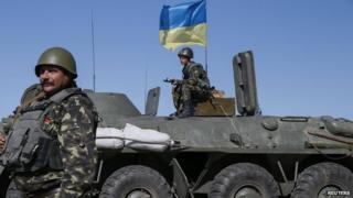 Ukrainian servicemen stand at a checkpoint near Debaltseve