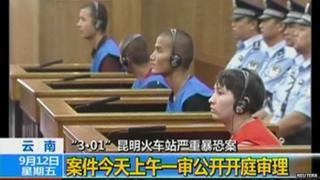 Defendants sit in front of police officers at a courtroom in Kunming City during the trial of four people accused of participating in an attack at a train station in southwestern China, in this still image taken from video on 12 September, 2014