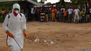 A public health worker in Liberia disinfects a courtyard as villagers watch.