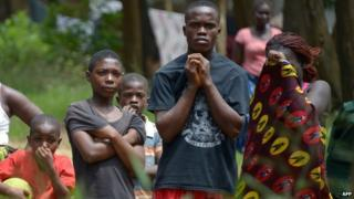 Liberians watch removal of Ebola victim's body