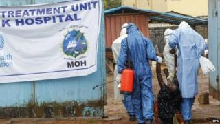 Health workers in Liberia take a suspected patient into a treatment centre
