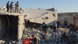 Residents of the Syrian village of Kfar Deria survey the damage after US missile strikes targeting the Khorasan Group (23 September 2014)
