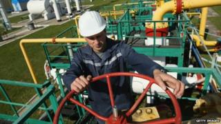 Darshava gas facility in Ukraine, man with manual wheel operating valve