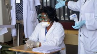 Health agents checking passengers leaving Liberia at the Roberts International Airport near Monrovia in August