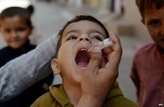A Pakistani child receives a polio vaccination drops from a health worker in Rawalpindi - 8 April 2014