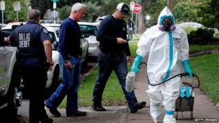 A man in protective clothing walks near the apartment of a second Dallas-area Ebola victim.