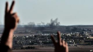 Kurds react as they watch smoke rising from the Syrian town of Kobane during fighting between Islamic State militants and Kurdish fighters (15 October 2014)