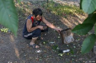 A man shows a dud cluster bomblet in Donetsk, Ukraine, 25 August