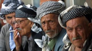 Kurdish men sit in the bazaar in Sulaimaniya, Iraq (17 October 2002)