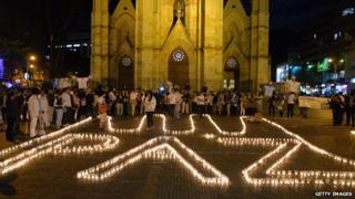 "Supporters of the peace process with the Farc form the word ""Peace"" with candles on the floor during an event in Bogota on 11 June, 2014"