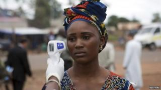 A woman's temperature is checked at the Guinea-Mali border, 2 October 2014