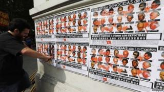 Man with poster showing 21 people tried for crimes at La Cacha in La Plata, Argentina 24 Oct 2014