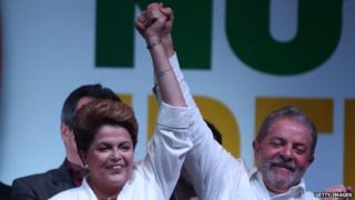 Dilma Rousseff celebrates with Brazil's former President Luiz Inacio Lula da Silva at a news conference in Brasilia, Brazil, Sunday, October 26, 2014