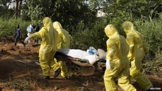 A burial team wearing protective clothing prepare the body of a person suspected to have died of the Ebola virus for interment in Freetown in Sierra Leone