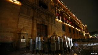 """Policemen block the wooden door of Mexican President Enrique Pena Nieto""""s ceremonial palace during a protest 8 Oct 2014"""