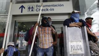 Masked protesters stand outside Acapulco airport on 10 November, 2014