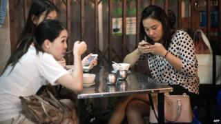 A group of young women eating food while using their smartphones