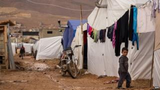 A young Syrian refugee walks past tents at the al-Nihaya camp in eastern Lebanon (25 November 2014)