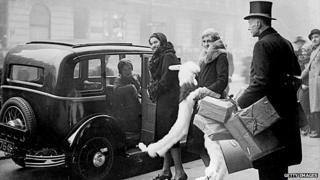 Christmas shoppers are helped into a taxi by the doorman at Whiteleys in west London in the 1920s