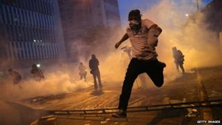 Protesters run from tear gas fired by the Venezuelan national guard during an anti-government demonstration on 27 February, 2014 in Caracas.