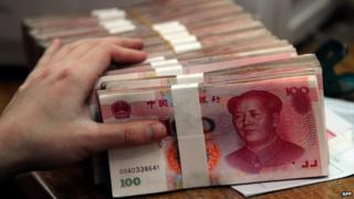 A person's hand on piles of 100-yuan notes