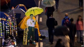 A cardboard cut-out of Chinese President Xi Jinping (C) carrying a yellow umbrella is seen at the pro-democracy movement's main protest site in the Admiralty district of Hong Kong on 2 December 2014