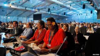 Delegates listen as COP 20 President and Peru's Environment Minister Manuel Pulgar Vidal speaks at the talks