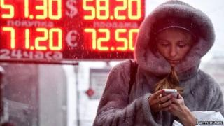 A woman walks past a board listing foreign currency rates against the Russian ruble in central Moscow