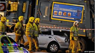 Firefighters walk close to a crashed bin lorry and a damaged car