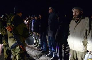 Rebel gunmen face Ukrainian prisoners prior to their release near Donetsk, 26 December