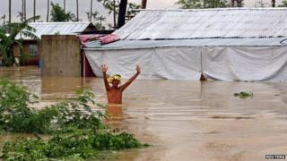 A resident wades through floodwaters brought on by heavy rains from tropical storm Jangmi, locally called Seniang, in Palo town, Samar province on 30 December 2014.