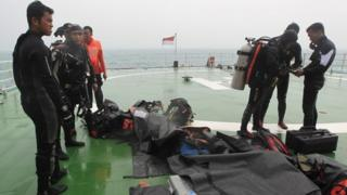 "Indonesian divers prepare their equipment aboard the Indonesian National Search and Rescue Agency (BASARNAS) ship ""KN Purworejo"" during a search operation for the crashed AirAsia plane in Pangkalan Bun, Central Borneo, Indonesia, on 04 January 2015"