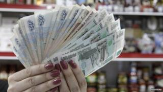 A cashier displays Russian rouble banknotes taken from a cash register at a local grocery store in Stavropol, southern Russia, January 7, 2015