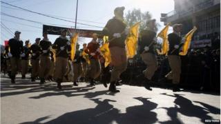 Lebanese Hezbollah supporters carry flags while marching during a religious procession in Nabatieh on 7 November 2014.