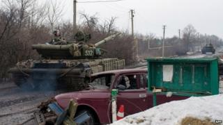 Ukrainian tanks pass damaged cars in village of Tonenke, near Donetsk airport. 19 Jan 2015
