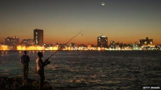 Men fish along the Malecon oceanfront underneath a fingernail moon January 2015 in Havana, Cuba