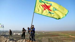 Kurdish Popular Protection Units (YPG) raise its flag on a hill overlooking Kobane (26 January 2015)