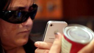 A blind woman taking a picture of a can