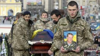 """Ukrainian soldiers carry the coffin bearing the body a member of self-defence battalion """"Aydar"""" during a funeral ceremony at Independence Square in central Kiev"""