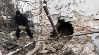 A man inspects his damaged home after shelling in Sartana village of Mariupol area, Ukraine